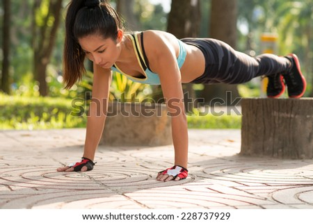 Fit girl doing straight arm plank exercise, her legs on stump - stock photo