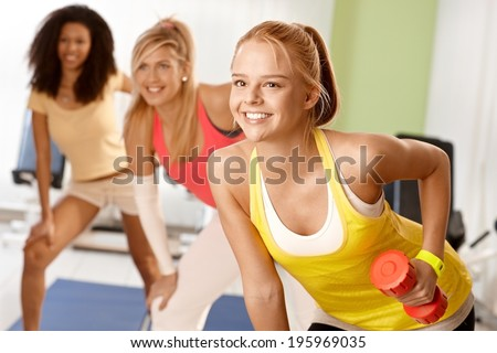 Fit girl exercising with dumbbells in group, smiling. - stock photo