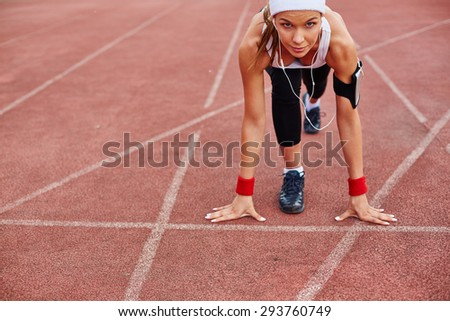 Fit girl in activewear standing at start line ready to run