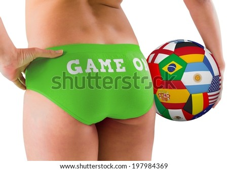 Fit girl in green bikini holding flag football on white background - stock photo