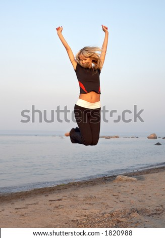 fit girl jumping at the seashore - stock photo