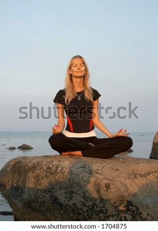 Fit girl meditating at the seashore - stock photo