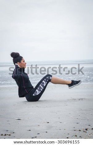 Fit girl working out on cold day at the beach - stock photo