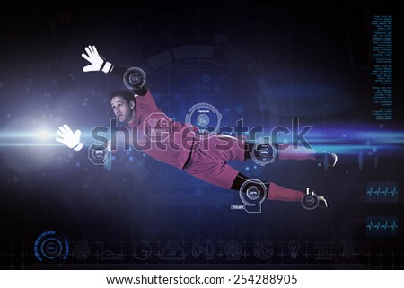 Fit goal keeper jumping up against blue dots on black background - stock photo
