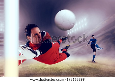 Fit goal keeper jumping up against football stadium - stock photo