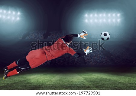 Fit goal keeper jumping up against large football stadium under blue sky - stock photo