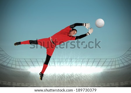 Fit goal keeper jumping up against large football stadium with spotlights - stock photo