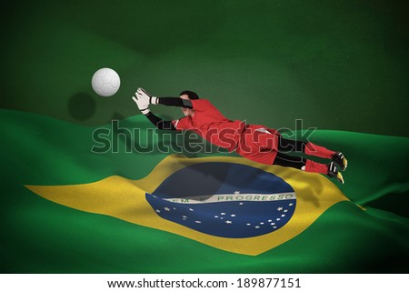 Fit goal keeper jumping up against white leather football with shadow - stock photo