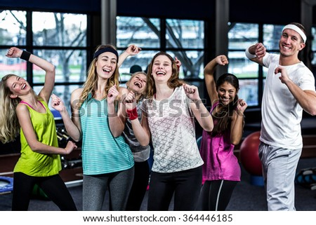 Fit group dancing and smiling in the gym - stock photo