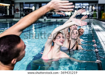 Fit group doing aerobical excercises in swimming pool - stock photo