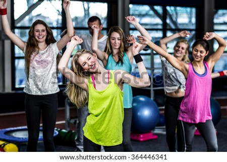Fit group exercising and smiling in the gym - stock photo