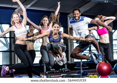 Fit group smiling and jumping in gym - stock photo