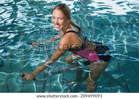 Fit happy blonde using underwater exercise bike in swimming pool at the leisure centre - stock photo