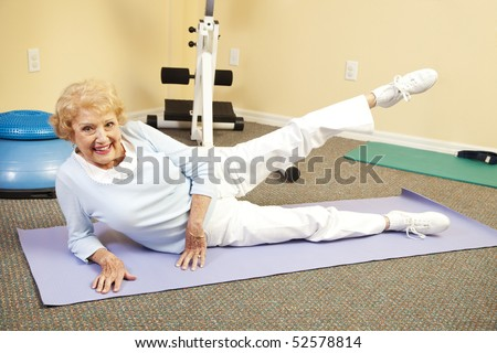 Fit happy senior woman doing stretching exercises on her yoga mat. - stock photo