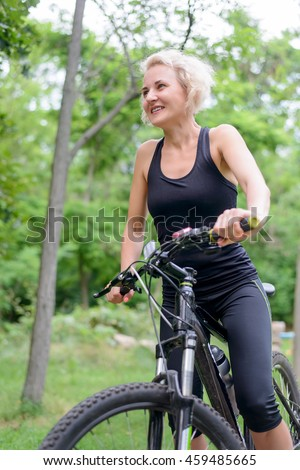 Fit healthy middle aged woman riding a bicycle outdoors in summer standing looking at the camera with a smile