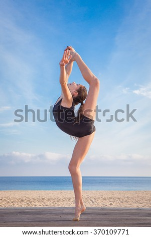 fit healthy young dancer doing stretching pose - stock photo
