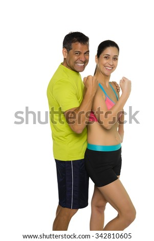 Fit Hispanic couple in workout attire flexing biscep - stock photo