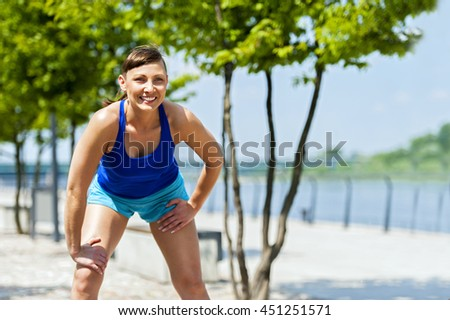 Fit jogger woman resting after run in city park. Smiling.