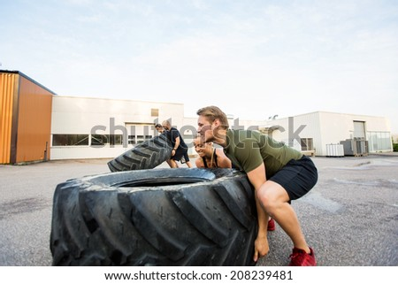 Fit male and female athletes doing tire-flip exercise outdoors - stock photo