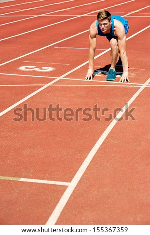 Fit male athlete on second running track - stock photo