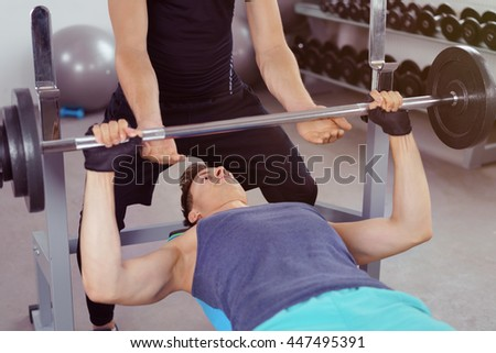 Fit male bodybuilder lifting weights in a gym assisted by a personal trainer ready to secure the barbell at the top of the lift - stock photo