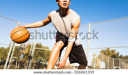 Fit male playing basketball outdoor - stock photo