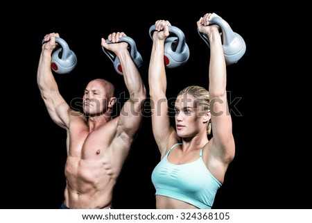 Fit man and woman lifting kettlebells against black background - stock photo