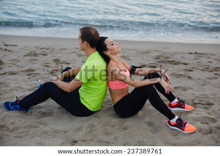 Fit man and woman resting after fitness training outdoors, young fitness couple having break after workout outdoors, two runners exhausted after run sitting on the beach enjoying beautiful evening - stock photo