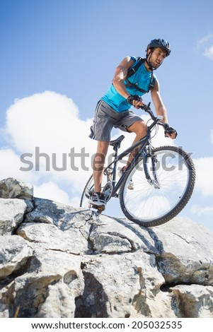 Fit man cycling on rocky terrain on a sunny day