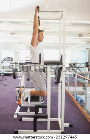 Fit man doing pull ups in fitness studio at the gym - stock photo