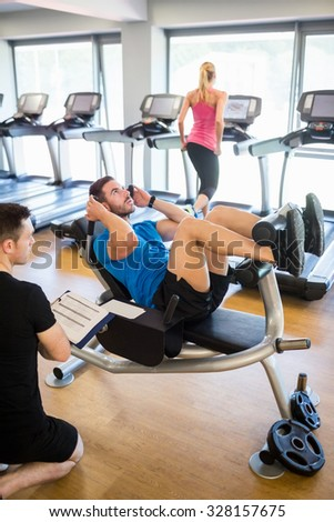 Fit man doing sit ups with trainer at the gym - stock photo