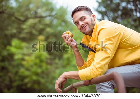 Fit man eating an apple in the countryside - stock photo