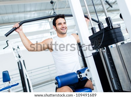 Fit man exercising at the gym on a machine - stock photo