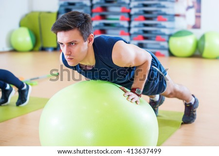 Fit man exercising with fit ball workout out arms Exercise training triceps and biceps doing push ups - stock photo