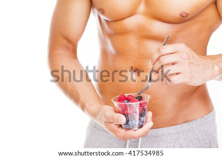 Fit man holding a bowl of fresh red fruits, isolated on white background - stock photo