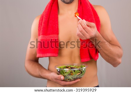 Fit man holding a bowl of fresh salad after a training day - stock photo