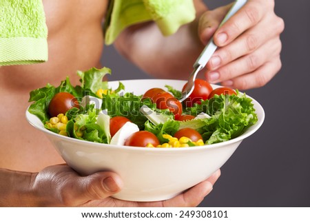 Fit man holding a bowl of fresh salad on grey background - stock photo