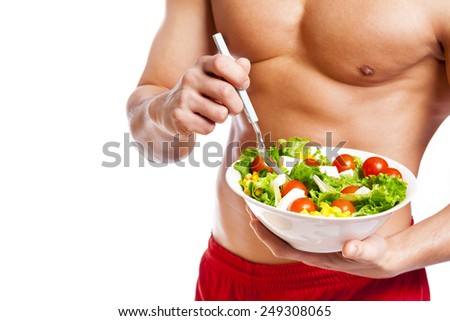 Fit man holding a bowl of fresh salad on white background - stock photo