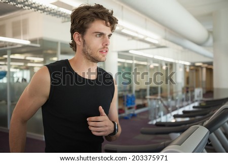 Fit man jogging on the treadmill at the gym - stock photo