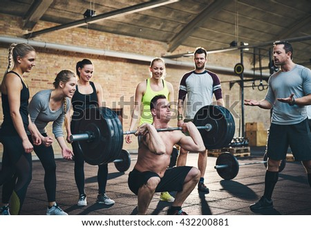 Fit man lifting barbells looking focused, working out in a gym with other people cheering him on in support - stock photo