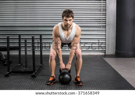 Fit man lifting dumbbells at crossfit gym - stock photo