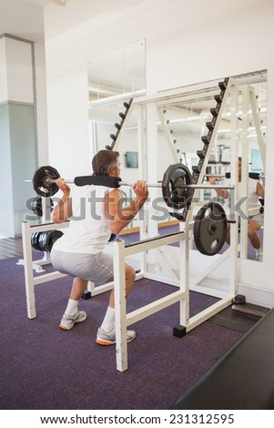 Fit man lifting heavy barbell at the gym - stock photo