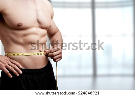 Fit man measuring his waist after a workout in the gym