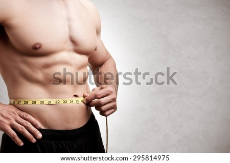 Fit man measuring his waist after a workout in the gym, isolated in a grey background - stock photo