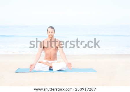 Fit man meditating on the beach - stock photo