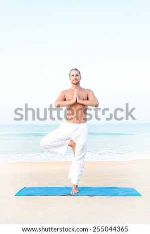 Fit man performing yoga pose at the beach - stock photo