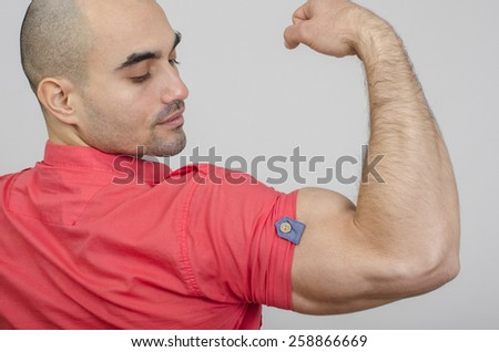 Fit man posing with his arm up showing his biceps. Bodybuilder showing his back and biceps muscles. - stock photo
