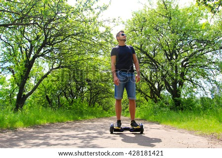 fit man riding an electrical scooter in the park - hoverboard, gyro scooter, smart balance wheel, personal eco transport