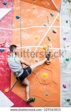Fit man rock climbing indoors at the gym - stock photo