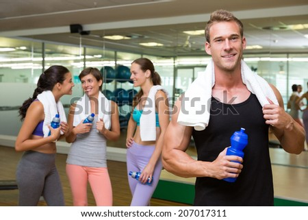Fit man smiling at camera in busy fitness studio at the gym - stock photo